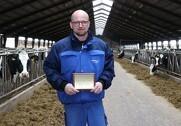 En stolt kvægproducent viser skiltet med de ti superkøer frem. Skiltet skal hænge sammen med de øvrige guldskilte inde på kontoret. Foto: Marianne Nørmark.